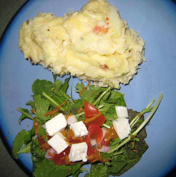 Mashed Potato Casserole with Smoked Gouda and Bacon with a spicy greens mix with red onions, tomatoes, chive flower feta and a Dijon mustard dressing