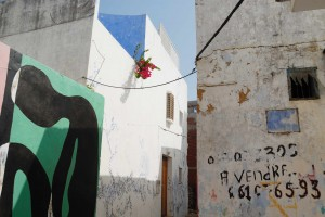 "A mural on the walls of Asilah's medina and a ""A vendre"" (""For Sale"") sign on the right."